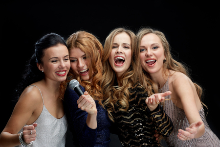 people laughing: holidays, friends, bachelorette party, nightlife and people concept - three women in evening dresses with microphone singing karaoke over black background