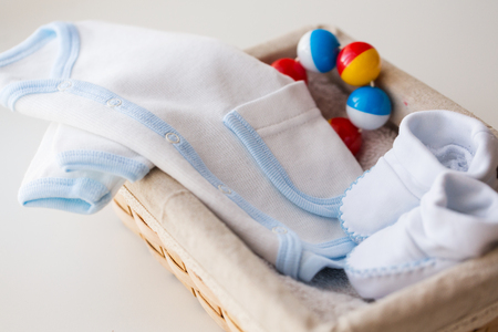 bootees: clothing, babyhood, motherhood and object concept - close up of white baby bootees with cardigan and rattle for newborn boy in basket on table
