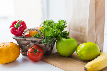 cooking, diet, vegetarian food and healthy eating concept - close up of basket with fresh ripe juicy vegetables, greens and fruits on kitchen table at home Stock Photo