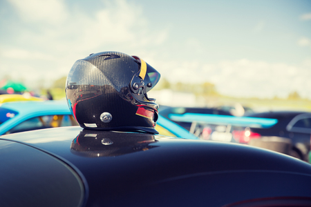 motosport: transportation, high speeds, racing and road concept - close up of car on autodrome or parking with helmet on roof top from back Stock Photo