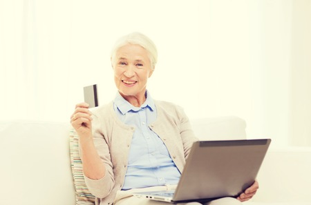 compute: technology, age and people concept - happy senior woman with laptop compute and credit or bank card r at home