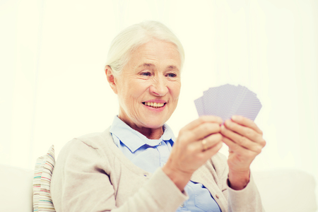 gamble: age, game, gamble, poker and people concept - happy smiling senior woman playing cards at home