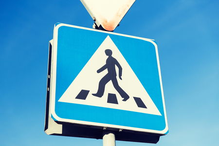 road safety: safety, traffic laws and highway code concept - close up of pedestrian crosswalk road sign Stock Photo