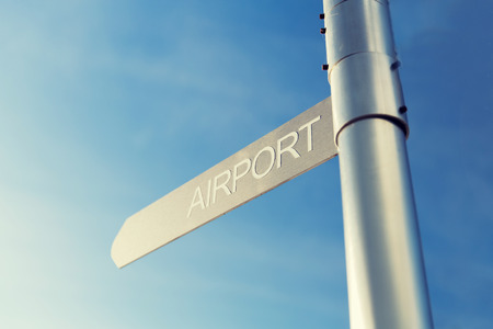 青空: 輸送、方向、場所、旅行と道路の概念に署名 - 青い空を背景に空港標識のクローズ アップ
