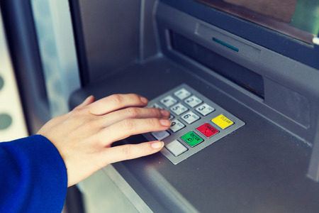 emoney: finance, technology, money and people concept - close up of hand entering pin code at cash machine