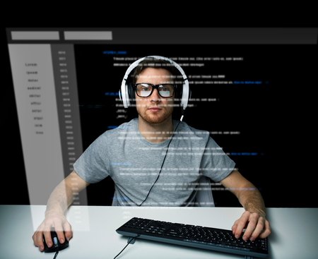 cyber terrorism: technology, cyberspace, virtual reality and people concept - man or hacker in headset and eyeglasses with keyboard hacking computer system or programming over vitual screen projection