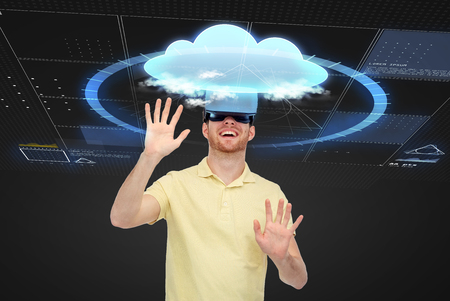 entertainment background: 3d technology, virtual reality, computing, entertainment and people concept - happy young man in virtual reality headset or 3d glasses playing game over black background with screens and cloud Stock Photo