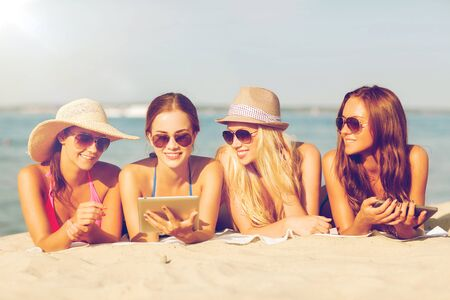 women smiling: summer vacation, travel, technology and people concept - group of smiling women in sunglasses with tablet pc computers lying on beach