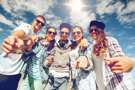 chill out: summer holidays and teenage concept - group of smiling teenagers in sunglasses hanging outside pointing finger at you Stock Photo