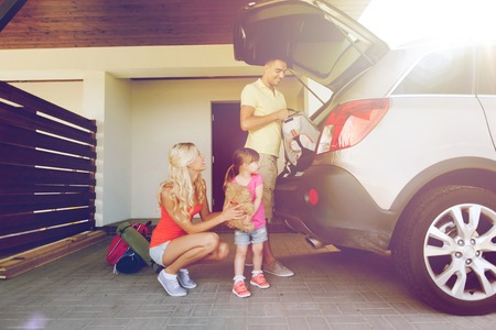 'young things': transport, leisure, travel, road trip and people concept - happy family packing things into car at home parking