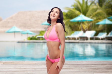 people, travel, tourism, swimwear and summer holidays concept - happy young woman in pink bikini swimsuit over swimming pool and sunbeds at exotic hotel resort background Stock Photo