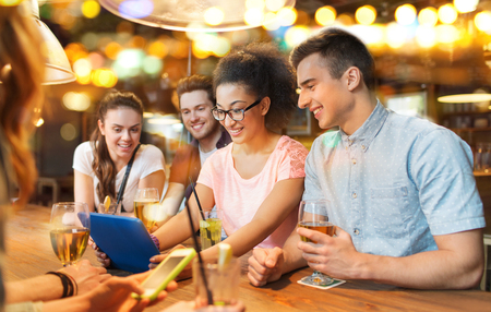 group of friends: people, leisure, friendship and communication concept - group of happy smiling friends with tablet pc computer and drinks at bar or pub
