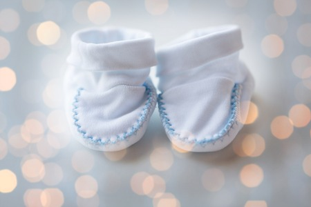bootees: clothing, babyhood, motherhood and object concept - close up of white baby bootees for newborn boy Stock Photo