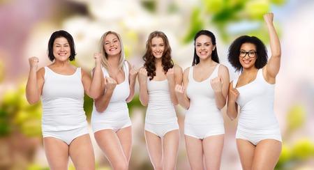 niñas en ropa interior: éxito, amistad, belleza, cuerpo positivo y concepto de la gente - grupo de mujeres felices del tamaño más en ropa interior blanca que celebra la victoria sobre fondo natural de manantial