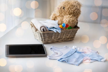 motherhood: babyhood, motherhood, clothing, technology and object concept - close up of baby clothes and toys for newborn boy in basket with tablet pc computer at home