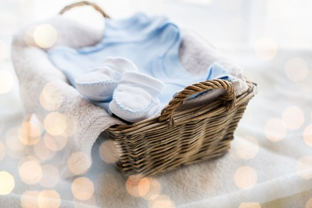 bootees: clothing, babyhood, motherhood and object concept - close up of white baby bootees with pile of clothes and towel for newborn boy in basket on table Stock Photo