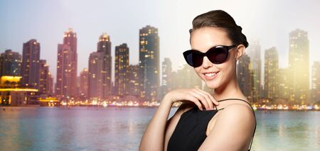 eyewear fashion: accessories, eyewear, fashion, people and luxury concept - beautiful young woman in elegant black sunglasses over night dubai city lights background