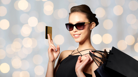 sale, finances, fashion, people and luxury concept - happy beautiful young woman in black sunglasses with credit card and shopping bags over holidays lights background