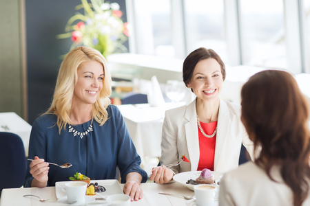 women smiling: people, food, communication and lifestyle concept - happy women eating dessert and talking at restaurant