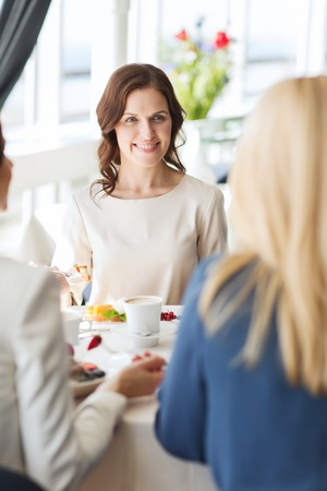 mensen, eten, communicatie en lifestyle concept - gelukkige vrouwen eten dessert en praten op restaurant Stockfoto