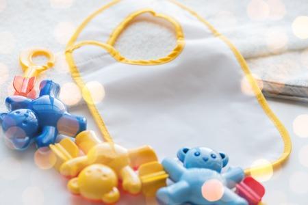 la infancia, la niñez, accesorios y objetos concepto - cerca de traqueteo del bebé y babero para niño recién nacido en la toalla