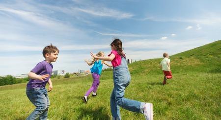 l'été, l'enfance, les loisirs et les gens concept - groupe d'enfants heureux de jouer tag jeu et en cours d'exécution sur le champ vert en plein air