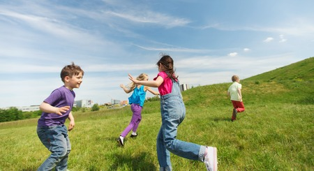 summer, childhood, leisure and people concept - group of happy kids playing tag game and running on green field outdoors Stok Fotoğraf