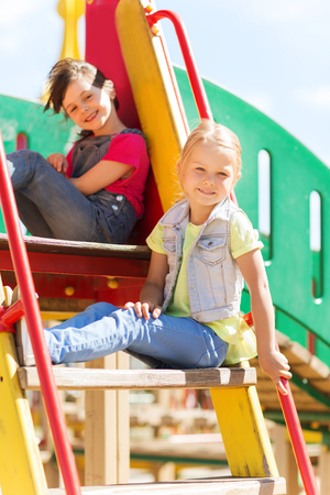 summer, childhood, leisure, friendship and people concept - happy kids on children playground climbing frame Stock Photo