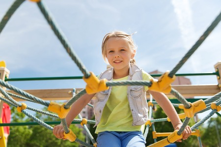 climbing frame: summer, childhood, leisure and people concept - happy little girl on children playground climbing frame