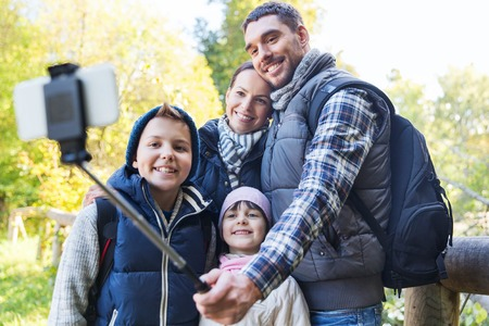 hiking stick: technology, travel, tourism, hike and people concept - happy family with backpacks taking picture by smartphone on selfie stick and hiking
