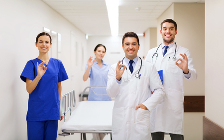 gurney: clinic, profession, people, health care and medicine concept - group of happy medics or doctors with gurney showing ok hand sign at hospital corridor