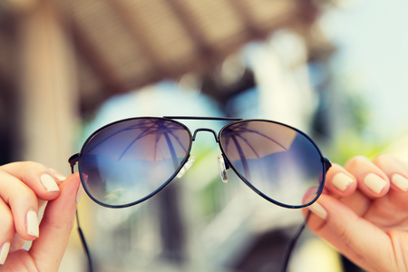 female police: travel, tourism, summer vacation, beach and fashion accessories concept - close up of woman hands holding shades or sunglasses with parasol reflection