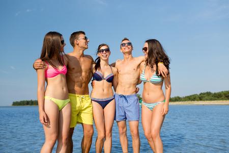 personas hablando: amistad, el mar, las vacaciones de verano, las vacaciones y la gente concepto - grupo de amigos sonrientes que usan trajes de baño y gafas de sol hablando y riendo en la playa