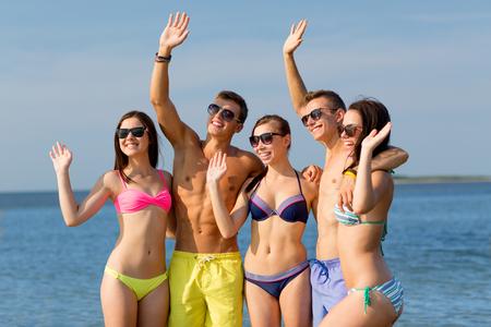 chicas adolescentes: amistad, el mar, las vacaciones, el gesto y la gente concepto - grupo de amigos sonrientes que usan trajes de baño y gafas de sol que agitan las manos en la playa