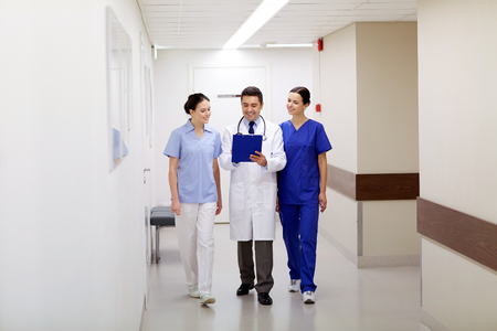 doctors smiling: clinic, profession, people, health care and medicine concept - group of smiling medics or doctors with clipboard walking along hospital corridor