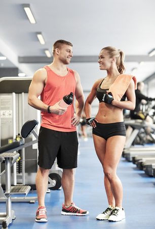 man gym: sport, fitness, lifestyle and people concept - smiling man and woman with protein shake bottle and towel talking in gym