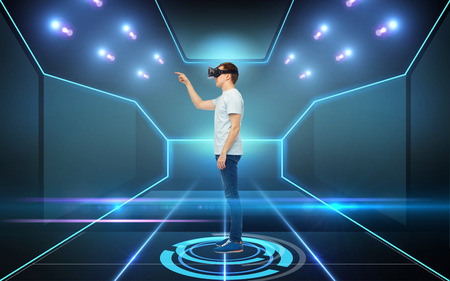 mediated: 3d technology, virtual reality, cyberspace and people concept - young man with virtual reality headset or 3d glasses playing game over black background and laser light