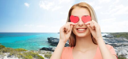 love, romance, valentines day and people concept - smiling young woman or teenage girl with red heart shapes on eyes over exotic tropical beach background