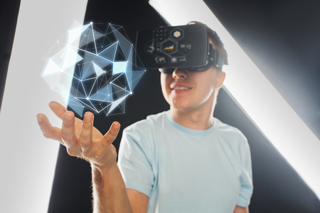 3d technology, virtual reality, science and people concept - close up of happy young man with virtual reality headset or 3d glasses playing game and holding polygonal shape projection