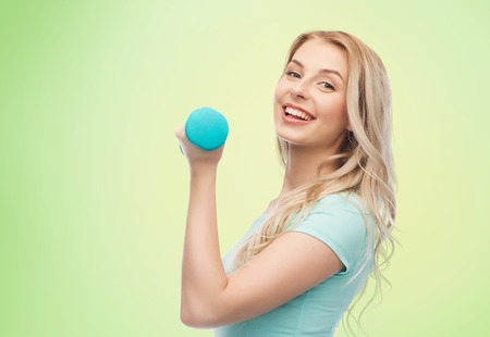 fitness, sport, exercising and people concept - smiling beautiful sporty woman with dumbbell over green natural background