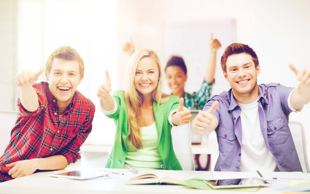 university admission: education concept - happy team of students showing thumbs up at school Stock Photo