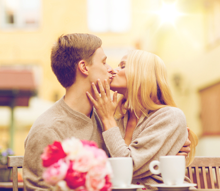 couple dating: summer holidays, love, travel, tourism, relationship and dating concept - romantic happy couple kissing in the cafe