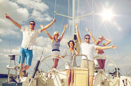 personas saludandose: vacaciones, viaje, mar, la amistad y la gente conceptuales - sonriendo amigos sentados en la cubierta del yate y un saludo Foto de archivo