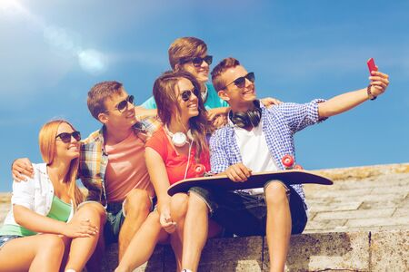 summer holidays: friendship, leisure, summer, technology and people concept - group of smiling friends with skateboard and smartphone making selfie outdoors