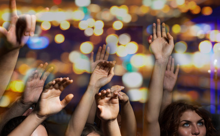 party, holidays, music, nightlife and people concept - close up of happy people at concert in night club waving hands Stock Photo