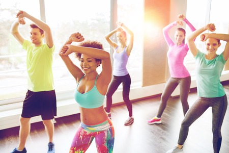 classes: fitness, sport, dance and lifestyle concept - group of smiling people with coach dancing zumba in gym or studio
