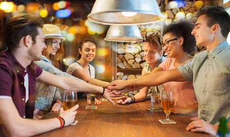 people, leisure, friendship and gesture concept - group of happy smiling friends with drinks putting hands on top of each other at bar or pub photo