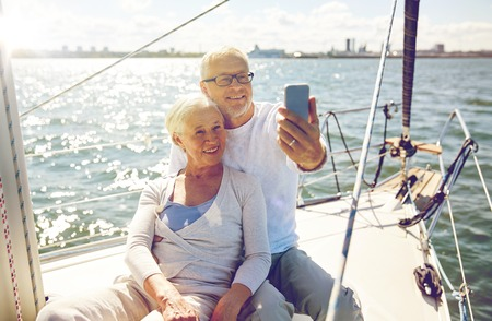 happy seniors: sailing, technology, tourism, travel and people concept - happy senior couple with smartphone taking selfie on sail boat or yacht deck floating in sea