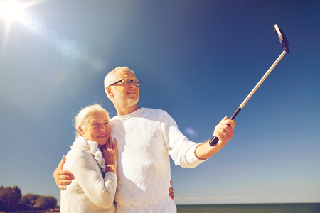 age, travel, tourism, technology and people concept - happy senior couple with smartphone on selfie stick taking picture on summer beach Stock Photo