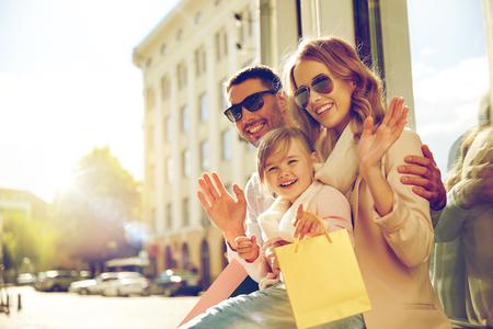 Ausverkauf, Konsum und Personen Konzept - glückliche Familie mit kleinem Kind und Einkaufstaschen winkenden Hände at Schaufenster in der Stadt
